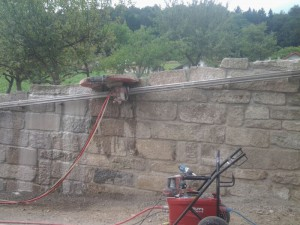 """2021-Startseite Baustellenbilder, Schneiden einer Granit-Gartenmauer. So wird eine """"saubere"""" Kante dem Gelände entsprechend erzeugt."""